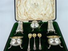 A VICTORIAN SILVER CONDIMENT SET, two salt and peppers with spoons, mustard with blue glass inlay and spoon; E S Barnsley & Co (Edwa...