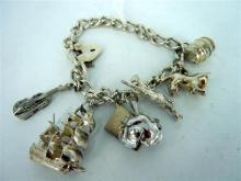 A SILVER CHARM BRACELET various charms including a sailing ship, barrel and violin closing to a padlock clasp. Weight 36.5g.