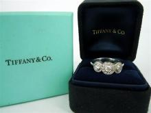 A TIFFANY & CO THREE STONE 'CIRCLET' DIAMOND RING, three round brilliant cut diamonds surrounded by an outer grain set circle of dia.