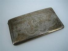 *A CHINESE EXPORT SILVER CARD CASE, curved for the pocket, engraved with a dragon on a 'planished' ground.