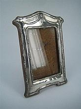 AN EDWARDIAN SILVER PHOTOGRAPH FRAME, Neo-Classical form, with swag cresting and ribbon & reed border; W.I.Broadway & Co., Birmingha...