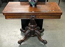 A VICTORIAN WALNUT GAMES TABLE, with fold over top and raised on four downswept legs.