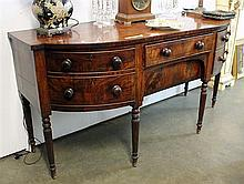 A GEORGIAN MAHOGANY SIDEBOARD, bow fronted, fitted with an arrangement of drawers, raised on six turned legs (BI).