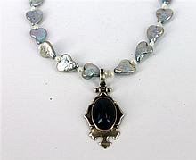 A FRESHWATER PEARL NECKLACE WITH A SILVER AND AGATE PENDANT FITTING