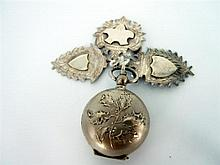 A SOVEREIGN CASE AND THREE SHIELD FOB MEDALLIONS, the white metal sovereign case with relief holly berry and leaf.