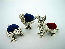 A GROUP OF SILVER ANIMAL PIN CUSHIONS including a pheasant, rabbit and a frog.