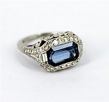 AN IMPRESSIVE PLATINUM ART DECO STYLE SAPPHIRE AND DIAMOND RING featuring an emerald cut blue sapphire of approx 3.27ct bordered by...