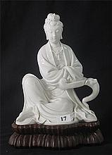 A CHINESE BLANC DE CHINE FIGURE OF QUAN YIN, seated on wooden base. ht. 26cm.