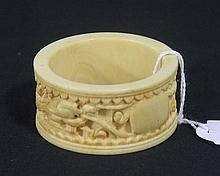 A CHINESE CARVED IVORY NAPKIN RING.