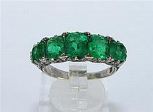A FIVE STONE EMERALD RING, graduated emeralds (heavily included) in an antique style mount; 18ct gold. Ring size O. Weight 5.5g.