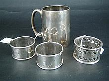 THREE SILVER SERVIETTE RINGS AND A CHRISTENING MUG including an Australian pair by Proud, Sydney c.1928. (4)