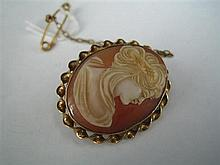 A SHELL CAMEO AND GOLD OVAL BROOCH, rim-set profile portrait brooch with ribbon-twist border; metal pin; gold safety chain; Rodd.