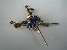 A PASTE AND METAL TROPHY BROOCH with crossed swords centred by a coronet.