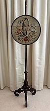 A VICTORIAN POLE SCREEN, with circular wool needlework depicting an eagle; turned column and carved tripod base. Panel diameter 40cm.
