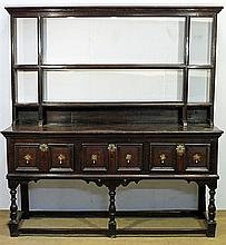 A CHARLES II OAK DRESSER, with plain pediment and galleried shelves, the base with three twin-panelled drawers with brass drop handl...