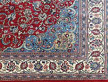 A CENTRAL PERSIAN KASHAN WOOL CARPET with a central medallion and arabesques on a red field. 384 x 297cm.