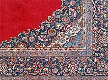 A SAROUK WOOL CARPET with a central medallion on a plain red field. 340 x 219cm.