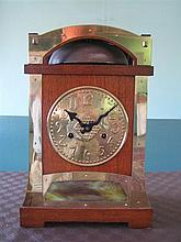 AN ARTS AND CRAFT MANTEL CLOCK, the brass-mounted oak case with stylized harbour bridge crest and inset with a slag-glass panel; two...