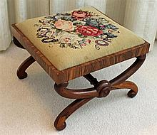 A VICTORIAN ROSEWOOD STOOL with wool needlework top and 'X'-shape supports united by a turned stretcher. 45 x 47cm.