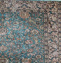 A CENTRAL PERSIAN ISFAHAN SILK RUG with a medallion motif on a blue field. 186 x 122cm.
