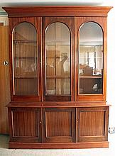 AN AUSTRALIAN CEDAR BOOKCASE with three glazed doors enclosing adjustable shelves; the base with cupboards enclosed by panel doors,...