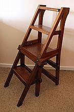 AN ARTS & CRAFTS OAK METAMORPHIC LIBRARY CHAIR. Height 90cm.
