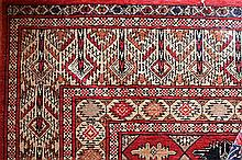 A TURKOMAN STYLE WOOL RUG with geometric medallions on a red field. 170 x 122cm.