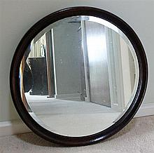 AN OAK FRAMED MIRROR with bevel-edged plate.