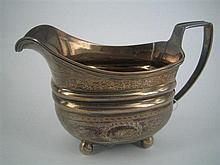 A GEORGE III SILVER CREAM JUG, oblong, with wrigglework and foliate engraved bands; on ball feet; London 1806. Height 8.5cm.