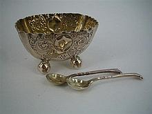 A VICTORIAN SILVER OPEN SALT AND A PAIR OF SPOONS, the salt oblong, with crimped rim, chased and embossed with foliate scrolls; Onsl...