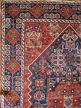 A PERSIAN WOOL RUG with geometric motifs in red and blue. 164 x 112cm.
