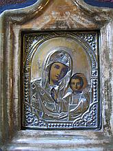 A 19th CENTURY RUSSIAN ICON depicting the Mother of God; brass oklad and glazed cabinet. 30 x 23cm.