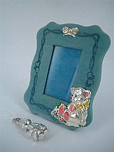 A SILVER BURROW-GUARDIAN RABBIT PENDANT AND A PHOTOGRAPH FRAME. (2)