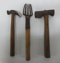 Collection of antique hand tools, serrated hand fork, axe and hammer