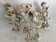 A set of four Capo-de-Monte porcelain putti, finely modelled with vines, wh