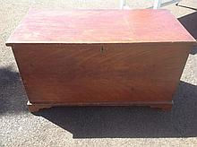 A large stained pine rectangular blanket box with hinged lid, raised on bra