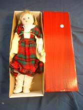porcelain doll in red and white and green outfit