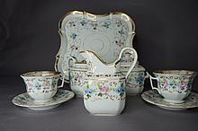 Service à déjeûner tête à tête en porcelaine blanche réhaussée d'or à décor de frises de fleurs épanouies comprenant un plateau  à bords mouvementés,