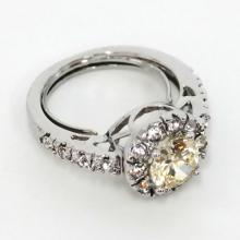 Silver tone solitaire ring with white 7.5 mm round CZ in the center surrounded by smaller white rhinestones