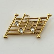 Gold tone music staff with notes white rhinestones pin brooch, signed NAPIER