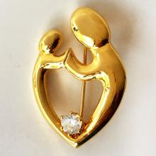 Gold plated brooch in abstract shape Mother and child with single prongs set white CZ