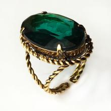 Gold plated ring with twisted wire and four prongs set oval faceted emerald color lab stone