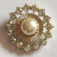 Silver tone brooch and gold plated ring in the center with faux mother of pearl and white rhinestones