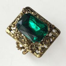 Gold plated filigree style ring with four prongs faceted rectangular emerald color stone