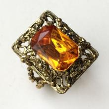 Gold plated filigree style ring with four prongs faceted emerald cut citrine color stone