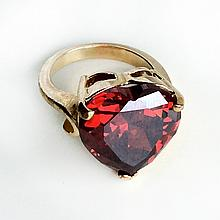 Gold tone heart shaped prongs set faceted garnet color ring