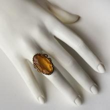 Gold plated ring with twisted wire and four prongs set oval faceted yellow citrine color lab stone
