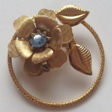Vintage gold plated textured pin brooch in shape of FLOWER WITH LEAVES with blu rhinestone