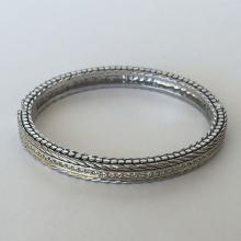 Silver tone black enamel textured bangle bracelet with 2 gold plated lines in the center and line of white rhinestones between