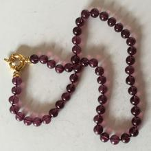 Round 8 mm amethyst color knotted beads necklace with gold plated toggle clasp
